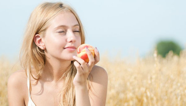 12535659 - young happy woman in wheat field with peach. summer picnic